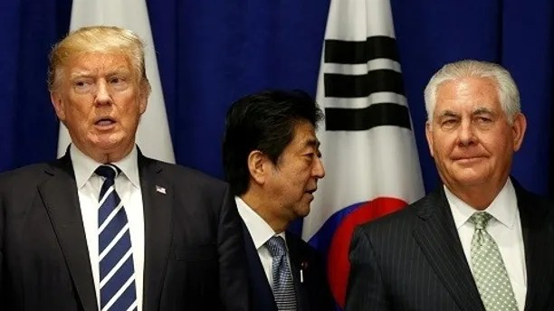 Japanese Prime Minister Shinzo Abe walks between U.S. President Donald Trump and U.S. Secretary of State Rex Tillerson at a lunch during the U.N. General Assembly in New York, U.S., September 21, 2017. REUTERS/Kevin Lamarque - RC131390FF40