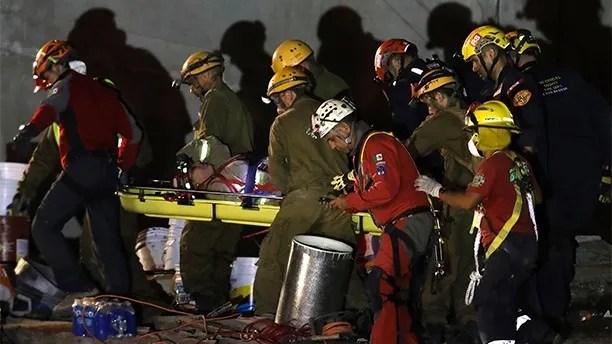 A female firefighter is carried out on a stretcher after spraining her ankle as rescue workers race against the clock to reach possible survivors trapped inside an office building in the Roma Norte neighborhood of Mexico City, in the early morning hours of Saturday, Sept. 23, 2017. A strong earthquake Tuesday toppled more than three dozen buildings in the capital, leaving dozens of people believed missing in this office building alone. (AP Photo/Rebecca Blackwell)