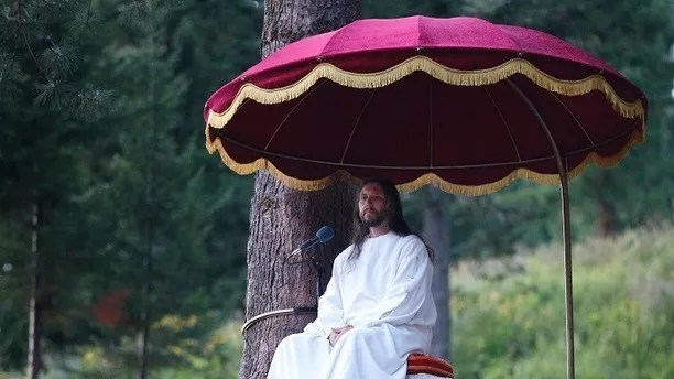 """Vissarion, who has proclaimed himself a new Christ, conducts a service during the """"Holiday of Good Fruit"""" feast in the village of Obitel Rassveta (Cloister of Sunrise), some 640 km (398 miles) southeast of Russia's Siberian city of Krasnoyarsk, August 18, 2010. Former police officer Vissarion gave up his original name of Sergei Torop and created a sect in 1991, whose members give up their property to join the construction of a so-called Sun City on the slopes of the mountain where their leader is. Russia's dominant Orthodox Church says sects like that of Vissarion, which have mushroomed after the collapse of the Soviet Union, ruin the moral health of the nation by indoctrinating their disciples and call for their ban. Picture taken August 18, 2010.  REUTERS/Ilya Naymushin  (RUSSIA - Tags: RELIGION SOCIETY IMAGES OF THE DAY) - GM1E68K1FD801"""