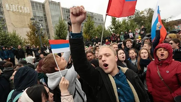 A demonstrator clenches his fist as other hold the Russian flag during a rally in Moscow, Russia, Saturday, Oct. 7, 2017. Opposition leader Alexei Navalny has worked to organize protests in support of his presidential bid across Russia on Saturday, President Vladimir Putin's birthday. (AP Photo/Ivan Sekretarev)