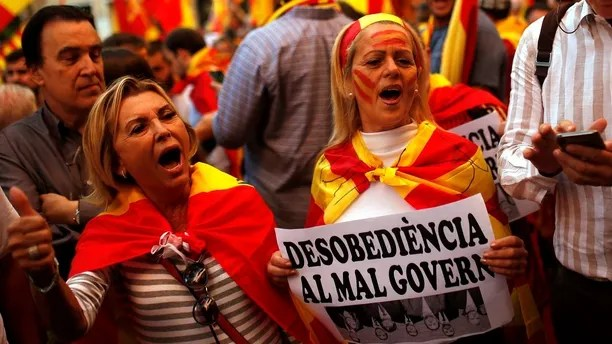 """Demonstrators shout slogans, some of them holding a banner reading in Catalan """"disobedience to the bad government"""", as they gather near a headquarters of federal police in Barcelona, Spain, Sunday Oct. 8, 2017. Demonstrators gathered early in Barcelona on Sunday ahead of a march to show support for the Spanish union and call on Catalonia not to declare independence. (AP Photo/Francisco Seco)"""