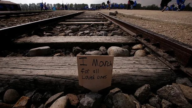 """A card is placed between railway tracks in the former Nazi death camp of Auschwitz-Birkenau (Auschwitz II) as thousands of people, mostly youth from all over the world gathered for the annual """"March of the Living"""" to commemorate the Holocaust in Brzezinka near Oswiecim, Poland May 5, 2016.  REUTERS/Kacper Pempel - S1BETCIEJIAA"""