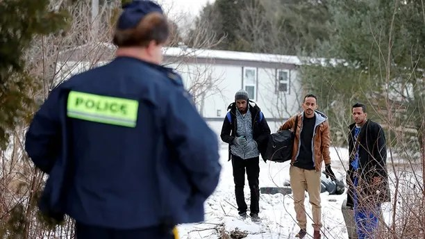"Three men who claimed to be from Sudan and were driven by taxi driver Curtis Seymour, are confronted by Royal Canadian Mounted Police (RCMP) as they prepare to cross illegally the U.S.-Canada border into Hemmingford, Quebec, Canada, March 4, 2017. The men were taken into custody after walking across the U.S.-Canada border. REUTERS/Christinne Muschi           SEARCH ""MUSCHI CABBIE"" FOR THIS STORY. SEARCH ""WIDER IMAGE"" FOR ALL STORIES. - RC19055660A0"