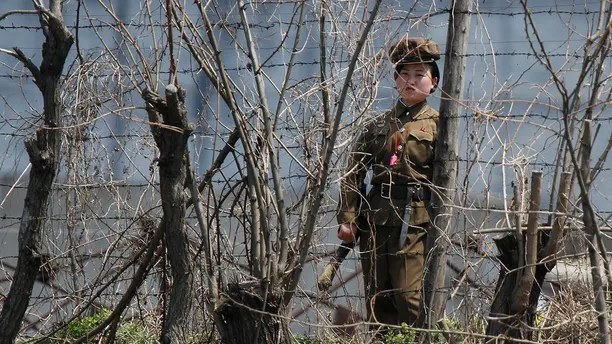 A North Korean prison policewoman stands guard behind fences at a jail on the banks of Yalu River near the Chongsong county of North Korea, opposite the Chinese border city of Dandong, May 8, 2011. Picture taken May 8, 2011. REUTERS/Jacky Chen (NORTH KOREA - Tags: MILITARY CRIME LAW POLITICS) - GM1E75912B601