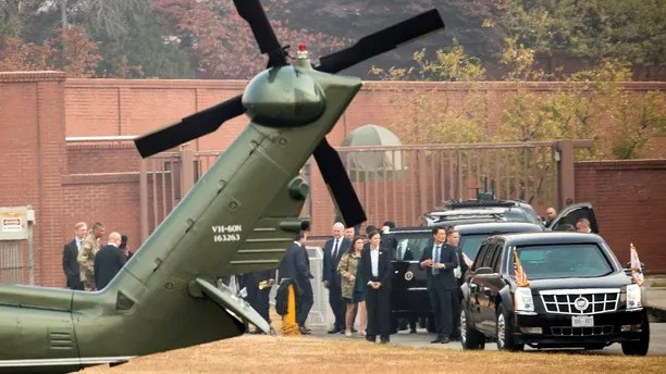 President Donald Trump sits in his presidential limo as Chief of Staff John Kelly, White House press secretary Sarah Huckabee Sanders, both at center, and other members of the administration try to wait out a bad weather call at U.S. Army Garrison Yongsan, Seoul, South Korea, Wednesday, Nov. 8, 2017. Marine One turned back because of a bad weather call just minutes away from visiting the Demilitarized Zone (DMZ), the tense military border between the two Koreas. Trump is on a five country trip through Asia traveling to Japan, South Korea, China, Vietnam and the Philippines. Also pictured is United States Forces Korea Commander Gen. Vincent Brooks, second from left. (AP Photo/Andrew Harnik)
