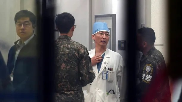 South Korean army soldiers talks with a medical doctor as he prepares to treat an unidentified injured person, unseen, believed to be a North Korean soldier, at a hospital in Suwon, South Korea, Monday, Nov. 13, 2017. North Korean soldiers shot at and wounded a fellow soldier who was crossing a jointly controlled area at the heavily guarded border to defect to South Korea on Monday, the South's military said. (Lee Jung-son/Newsis via AP)