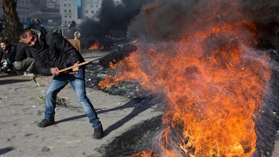 A Palestinian protester burns tires to protest President Trump's decision to move the U.S. Embassy in Israel to Jerusalem.