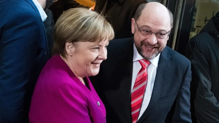 German chancellor and head of the Christian Democrats, Angela Merkel, left, and the leader of Germany's Social Democratic party, Martin Schulz, shake hands in Berlin, Sunday, Jan. 7, 2018.