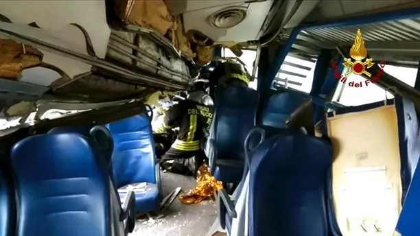 This image provided by the Italian firefighters Vigili del Fuoco shows firefighters inside a train wagon trying to help a passenger out after the train derailed at the station of Pioltello Limito, on the outskirts of Milan, Italy, Thursday, Jan. 25, 2018. Carabinieri say a commuter train carrying hundreds of people has derailed in northern Italy, killing at least two people and seriously injuring at least 10. (Italian Firefighters Vigili del Fuoco via AP)