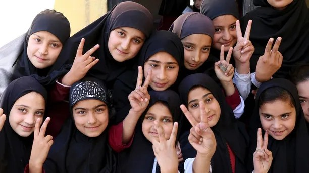 Students of the school of Nobel Peace Prize winner Malala Yousafzai flash victory sign in her hometown of Swat Valley in Pakistan, Friday, March 30, 2018. A Pakistani women's activist says Malala Yousafzai, who is back in Pakistan for the first time since the Taliban shot her in 2012, is hoping to visit her Swat Valley hometown but that the trip depends on security clearances from the government.(AP Photo/Naveed Ali)