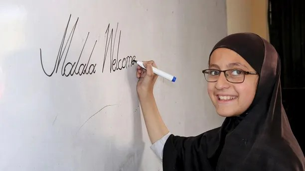 A Pakistani student of the school of Nobel Peace Prize winner Malala Yousafzai writes on a board writes on a board, in her hometown of Swat Valley in Pakistan, Friday, March 30, 2018. A Pakistani women's activist says Malala Yousafzai, who is back in Pakistan for the first time since the Taliban shot her in 2012, is hoping to visit her Swat Valley hometown but that the trip depends on security clearances from the government.(AP Photo/Naveed Ali)