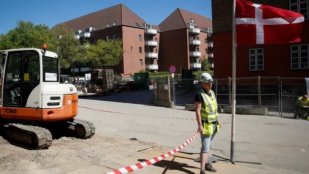 """A worker stands beside a Danish flag on a construction site of new housing being built next to Mjolnerparken, a housing estate that features on the Danish government's """"Ghetto List"""", in Copenhagen, Denmark, May 8, 2018. REUTERS/Andrew Kelly SEARCH """"DENMARK GHETTO"""" FOR THIS STORY. SEARCH """"WIDER IMAGE"""" FOR ALL STORIES. THE IMAGES SHOULD ONLY BE USED TOGETHER WITH THE STORY - NO STAND-ALONE USES. - RC1AE1788040"""