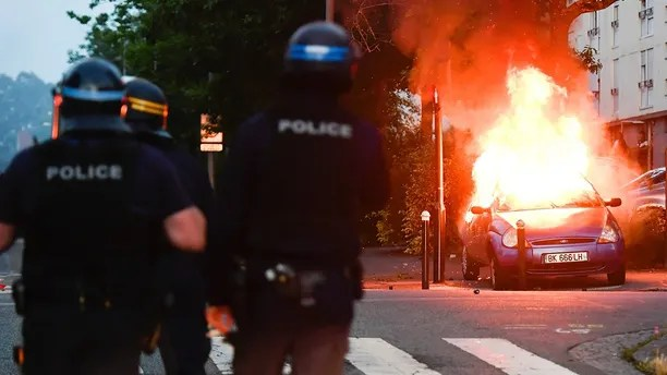 Police officers watch a car burning in Nantes, western France, Tuesday July 3, 2018. French authorities called for calm in France's western city of Nantes after scuffles with police broke out overnight, after police shot at a young driver who was trying to avoid a control. (AP Photo/Franck Dubray)