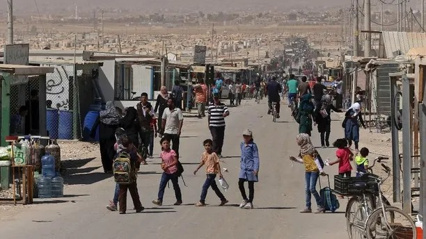 In this Thursday, Oct. 1, 2015 photo, Syrian refugees stroll on the main street of the U.N.-run Zaatari refugee camp near Mafraq, northern Jordan. More than 4 million Syrians fled civil war in their country, now in its fifth year. Most settled in Turkey, Lebanon and Jordan. Banned from working legally, they depend on aid and odd jobs. (AP Photo/Raad Adayleh)