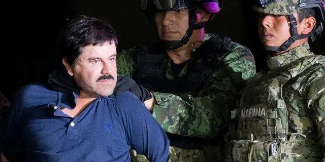 "In this Jan. 8, 2016 file photo, a handcuffed Joaquin ""El Chapo"" Guzman is made to face the press as he is escorted to a helicopter by Mexican soldiers and marines at a federal hangar in Mexico City."