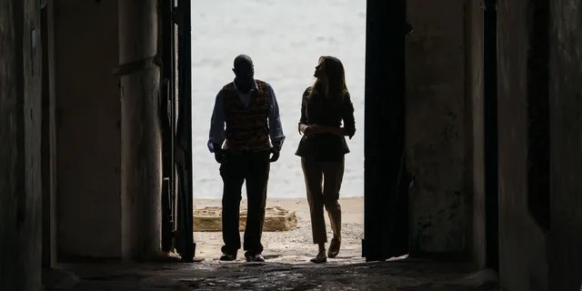 """First lady Melania Trump looks up as she walks through the """"Door Of No Return"""" with museum educator Kwesi Essel-Blankson as she visits Cape Coast Castle in Ghana on Oct. 3, 2018. (AP Photo/Carolyn Kaster)"""