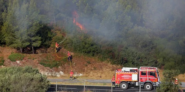 Firefighters control flames approaching a road outside the village of Charneca, in the Sintra national park, west of Lisbon, Sunday, Oct. 7, 2018. Over 700 firefighters were battling a forest fire that started overnight about 40 kilometers (25 miles) west of Lisbon. (AP Photo/Armando Franca)