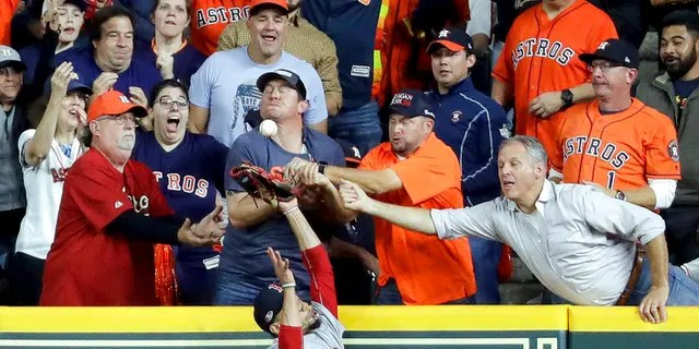 FILE: Fans interfere with Boston Red Sox right fielder Mookie Betts trying to catch a ball hit by Houston Astros' Jose Altuve.