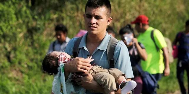 Un jeune homme porte un enfant dans la caravane des Honduriens.