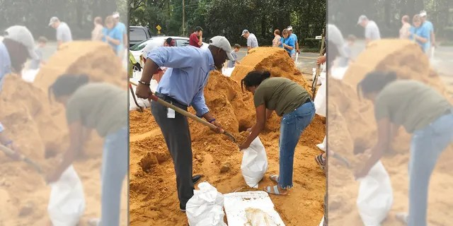 Tallahassee Mayor and Democratic gubernatorial candidate, Andrew Gillum, left, helps Eboni Sipling fill up sandbags in Tallahassee, Fla., Monday, Oct. 8, 2018.