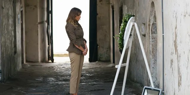 """First lady Melania Trump pauses after placing a wreath near at one of the dungeon doors at Cape Coast Castle in Cape Coast, Ghana, Wednesday, Oct. 3. Cape Coast Castle was a """"slave castle"""" used in the trans-Atlantic slave trade. Behind her is the """"Door of No Return."""""""