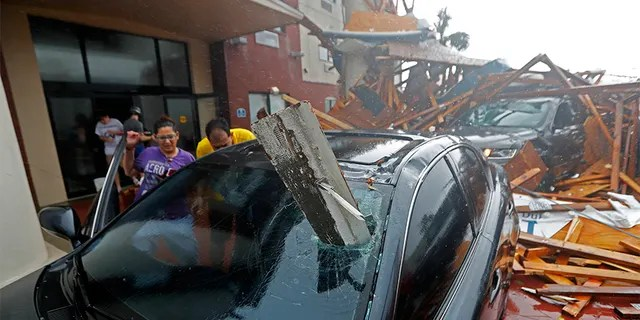 A woman checks on her vehicle as Hurricane Michael passes through, after the hotel canopy had just collapsed, in Panama City Beach on Wednesday.