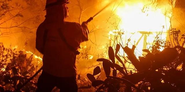 Firefighters battle the Woolsey Fire in Malibu, Calif.