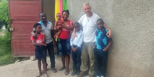 """Barclay Stuart with John """"Little John"""" Olivier's family in Haiti before the nine-year-old Haitian received the life-saving surgery."""