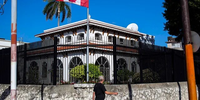 FILE - In this April 17, 2018 file photo, a man walks beside Canada's embassy in Havana, Cuba.