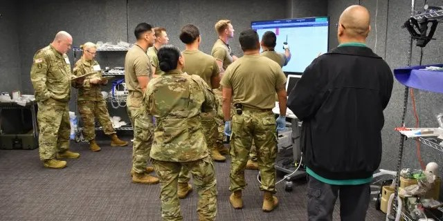 Before patient arrival, test participants with the 44th Medical Brigade studied patient information on the Medical Hands-free Unified Broadcast device. (Ashley Force, U.S. Army)