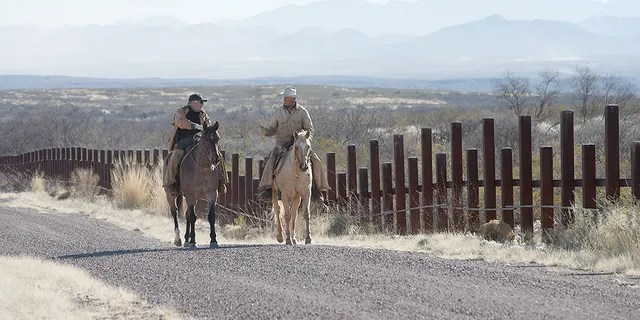 Howard Buffett speaking to a rancher whose property sits alongside border fencing in Arizona.