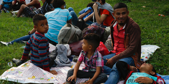 Freddy Rivas, second right, of Tocoa, Honduras, sits with his sons Josue, left, and Elkin, center, and his brother Mario, as they wait with scores of other migrants hoping to join a caravan to travel to the U.S. border, in San Pedro Sula, Honduras, Monday, Jan. 14, 2019. Hundreds of Hondurans hoping to reach the U.S. began gathering at a main bus station in San Pedro Sula Monday night to join a caravan that had been advertised in social media as departing in the early hours of Tuesday morning. (AP Photo/Delmer Martinez)