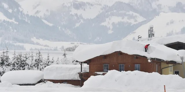A man cleans snow from a roof on Saturday, Jan. 12, 2019 in St. Jakob, Austrian province of Tyrol.