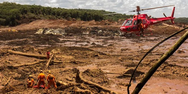 On Tuesday in Brumadinho, firefighters recover a body with a chopper's assistance. (Photo by Rodney Costa/picture alliance via Getty Images)