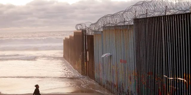 "FILE - In this Jan. 9, 2019 file photo, a woman walks on the beach next to the border wall topped with razor wire in Tijuana, Mexico. What started as an online fundraiser to provide President Donald Trump with donations for his southern border wall has morphed into a new foundation whose members vow to build a wall themselves. The ""We The People Will Build the Wall"" campaign has surpassed $20 million since it was created in December by Air Force veteran and triple amputee Brian Kolfage. The campaign has received almost 350,000 donations even as wall opponents derided the effort and after the longest government shutdown in U.S. history ended with Congress refusing Trump's demand for billions in wall funding. (AP Photo/Gregory Bull, File)"