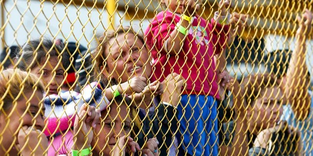 Central American immigrant families looking out through the fence of a shelter in Piedras Negras, Mexico, last month. (Jerry Lara/The San Antonio Express-News via AP, File)