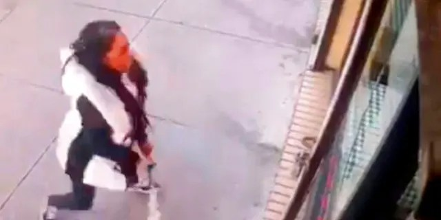 """A woman smashes the windows of """"Back Home Restaurant"""" in the Bronx borough of New York."""