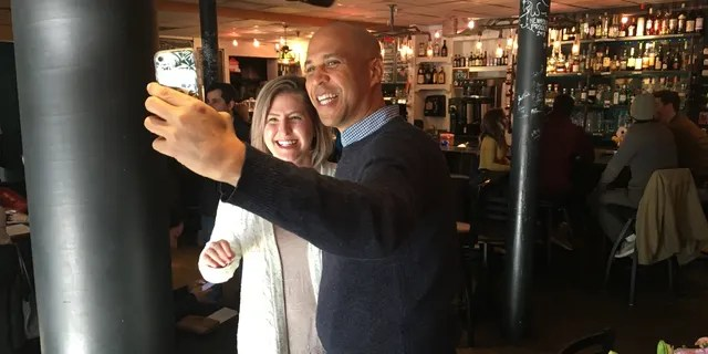 Sen. Cory Booker taking a photo with a voter in Nashua, N.H., in December 2018.