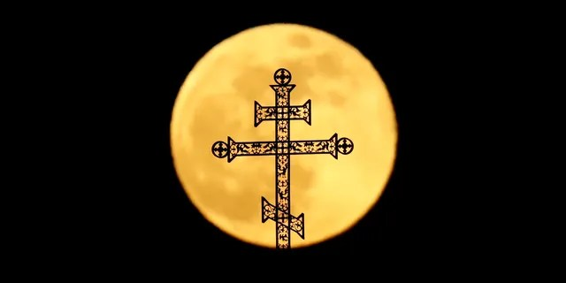 The full moon rises behind a steeple with crosses of an Orthodox church in Minsk, Belarus, Tuesday, Feb. 19, 2019.
