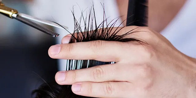 Close-up photo of barber's hands with scissors cutting hair