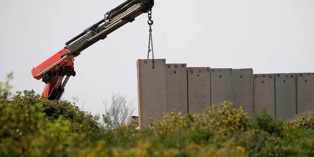 An Israeli crane builds a wall near the border, seen from Lebanon, near the village of Naqoura, March 6, 2018.