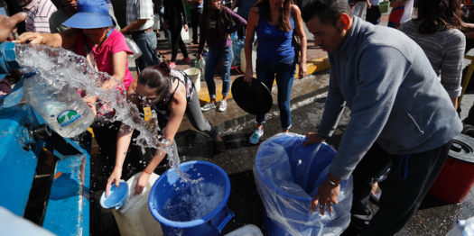 People collect water from a truck that delivers water during rolling blackouts, in Caracas, Venezuela, Tuesday, March 12, 2019.