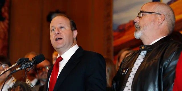 Colorado Gov. Jared Polis, left, speaks as Rep. Tom Sullivan, D-Aurora, looks on before Polis signs a bill to allow Colorado to become the 15th state in the union to adopt a