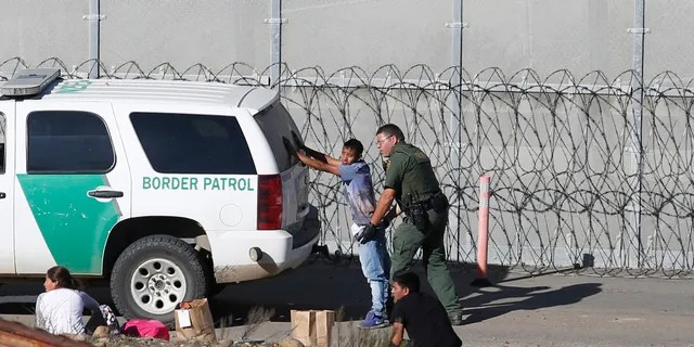"""Last year, Honduran asylum seekers were taken into custody by Border Patrol agents after the group crossed the U.S. border wall into San Diego, Calif. Detained asylum seekers who have shown they have a credible fear of returning to their country will no longer be able to ask a judge to grant them bond. U.S. Attorney General William Barr decided in April 2019, that asylum seekers who clear a """"credible fear"""" interview and are facing removal don't have the right to be released on bond while their cases are pending and will have to wait in detention until their case is adjudicated. (AP Photo/Moises Castillo, File)"""