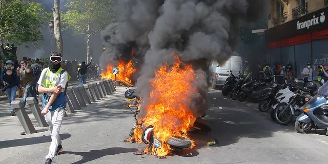 A man runs by a burning motorbike during a demonstration in Paris, Saturday.