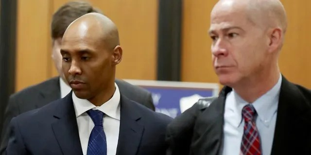 Former Minneapolis police officer Mohamed Noor, center, is accompanied by his attorneys Peter Wold, not pictured, and Thomas Plunkett, right, as he walks towards the Hennepin County Government Center for opening arguments of his trial Tuesday, April 9, 2019.