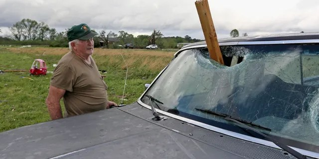 A man looks at a piece of wood blown through the windshield of his truck in Hamilton, Miss., After a storm swept through the area on Sunday, April 14, 2019.