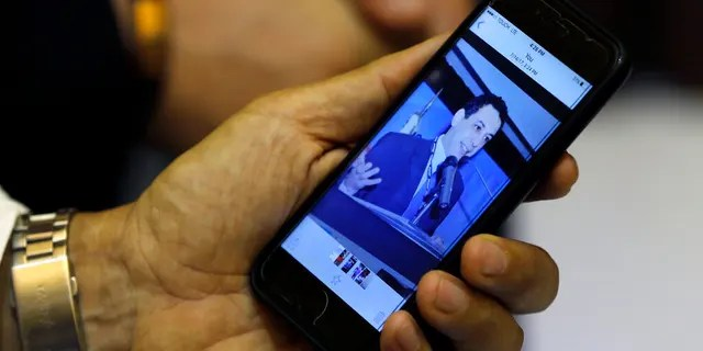 FILE: Ziad Zakka, brother of Nizar Zakka who is imprisoned in Iran, shows a photo of his brother on his cellular telephone in Beirut, Lebanon.