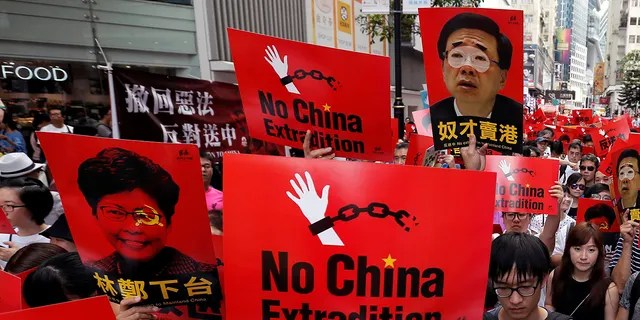 Demonstrators hold signs during a protest to demand authorities scrap a proposed extradition bill with China, in Hong Kong, China June 9, 2019.