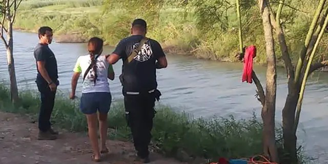 Tania Vanessa Ávalos of El Salvador, center left, is assisted by Mexican authorities after her husband and nearly two-year-old daughter were swept away by the current while trying to cross the Rio Grande to Brownsville, Texas, in Matamoros, Mexico, on Sunday. (AP)